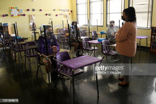 Teacher speaks with students as they return to in-person learning at St. Anthony Catholic High School during the Covid-19 pandemic on March 24, 2021...