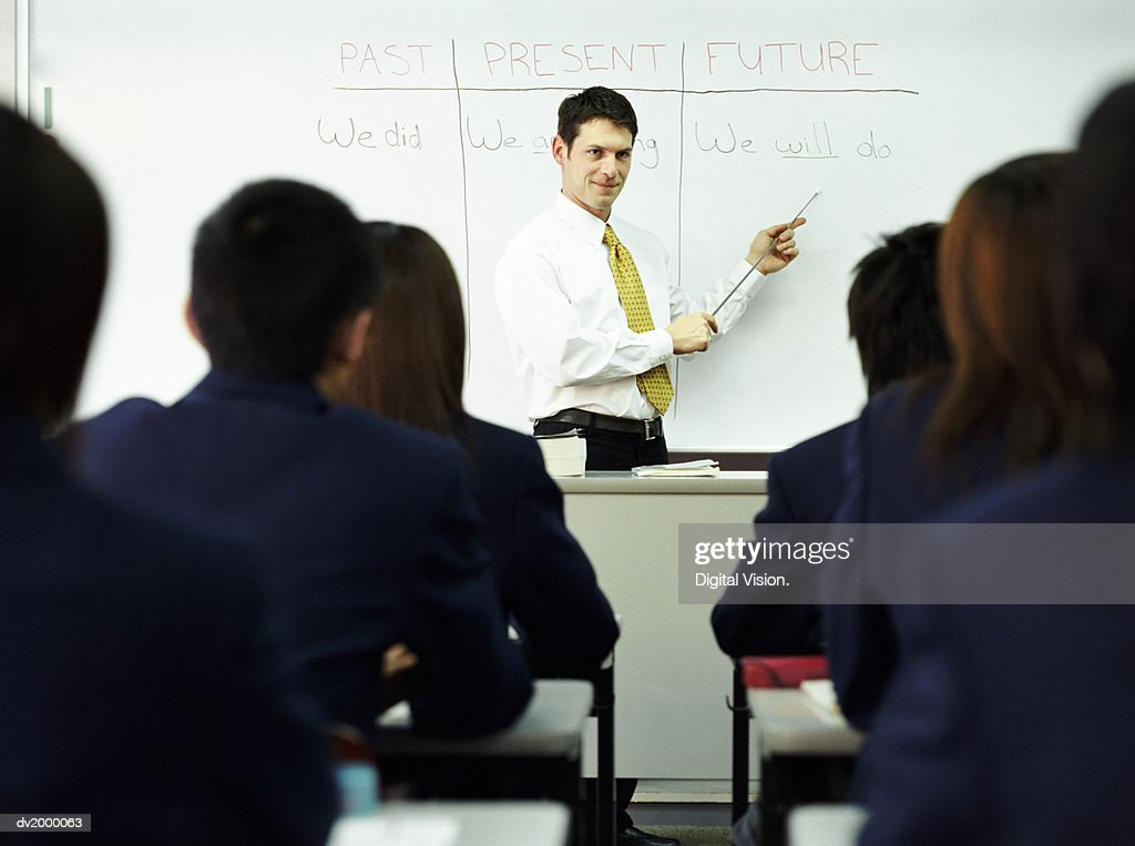 Teacher Standing at the Head of a Class Pointing to Words on a White Board : Stock Photo