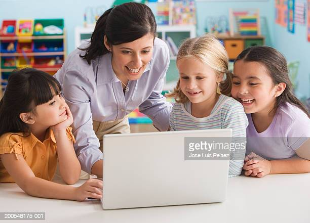 Teacher standing by students (4-7) using laptop, smiling