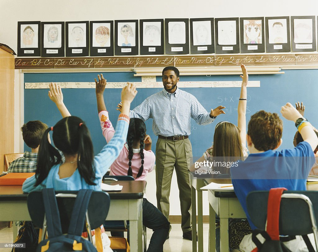 Teacher Standing in Front of a Class of Raised Hands : Stock Photo
