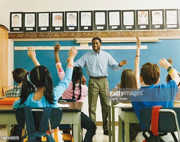 teacher standing in front of a class of raised hands - lehrkraft stock-fotos und bilder