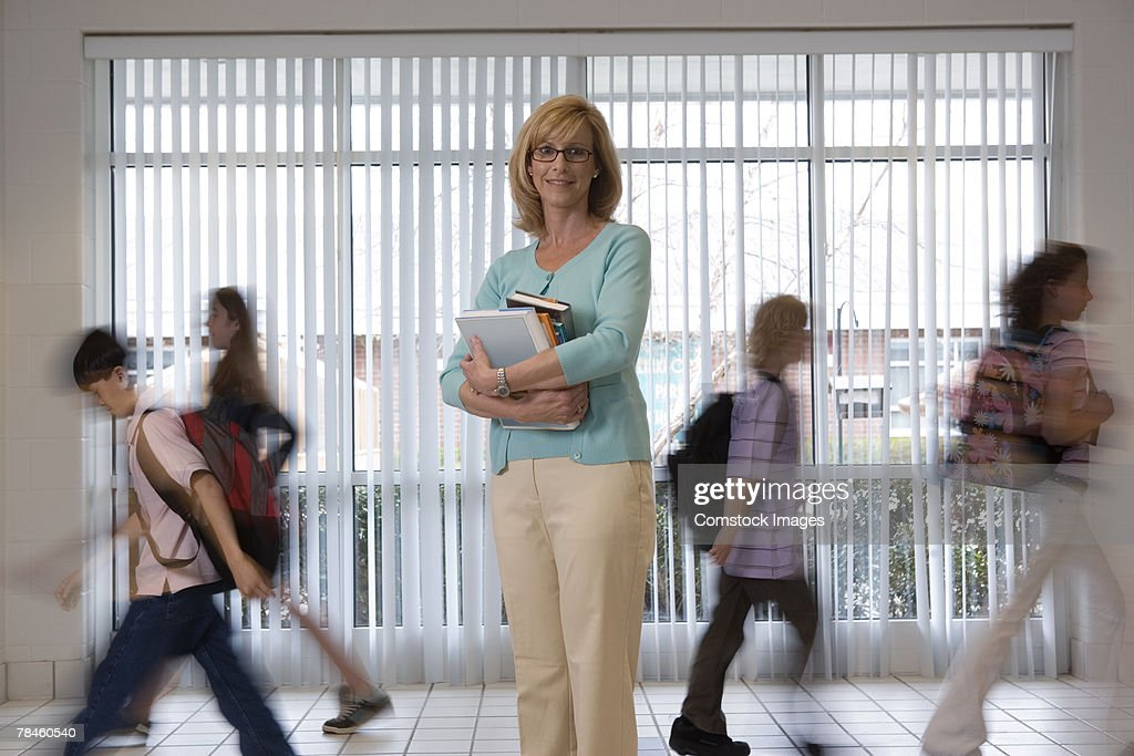 Teacher standing in hallway and students walking past : Stock Photo