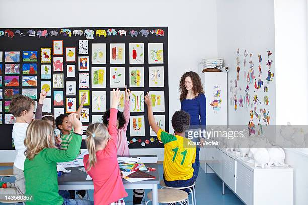 Teacher standing infront of kids with raised hands