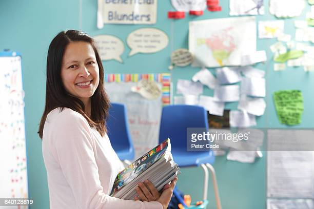 teacher stood in classroom holding books - teacher stock pictures, royalty-free photos & images