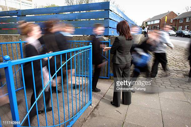A teacher supervises children leaving Darwen Vale High School at home time where staff are preparing to strike tomorrow over pupil discipline issues...