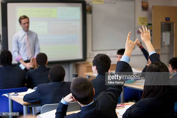 Teacher takes a history class as pupils raise their hands at Pimlico Academy, a modern secondary school in London, UK. Students education here is...