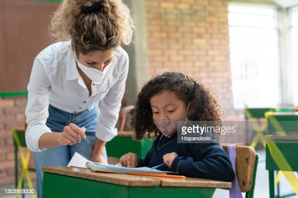 teacher talking to a girl at the school and wearing facemasks during the pandemic - school detention stock pictures, royalty-free photos & images
