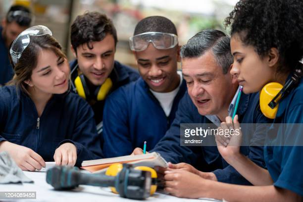 teacher talking to a group of industrial design students - trainee stock pictures, royalty-free photos & images