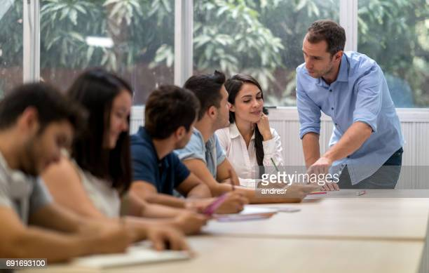 teacher talking to a group of students in class - college professor stock photos and pictures