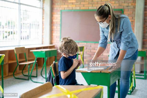teacher talking to a young student at school and wearing facemasks during the covid-19 pandemic - school detention stock pictures, royalty-free photos & images