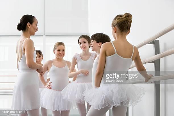 Teacher talking to boy and girls (3-13) in ballet class
