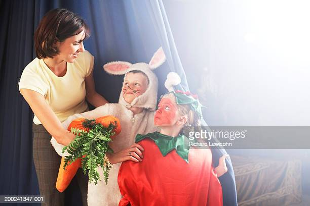 teacher talking to children (5-7) in costumes standing behind stage curtain - school play stock photos and pictures