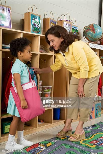 Teacher talking to girl (4-5) in classroom
