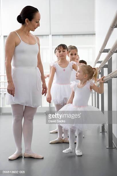 Teacher talking to girl (2-4) standing at bar in ballet class