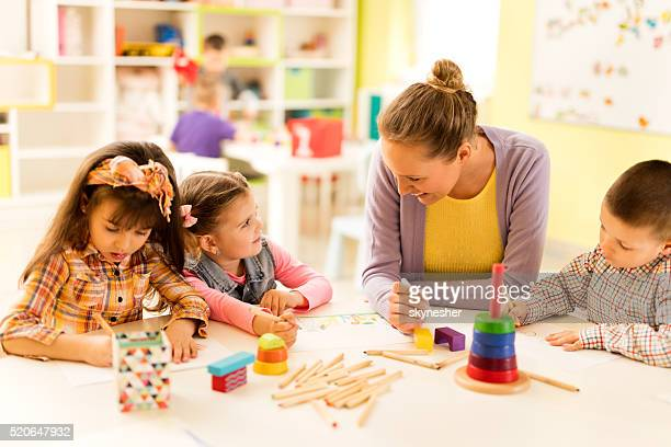 Teacher talking to little girl during art class in kindergarten.