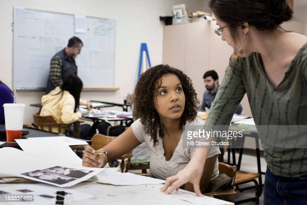 Teacher talking to student in art class