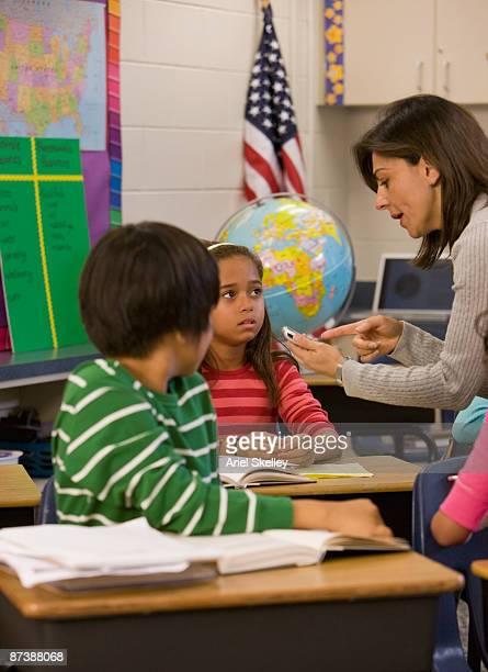 teacher talking to student in classroom - ariel rebel stock-fotos und bilder