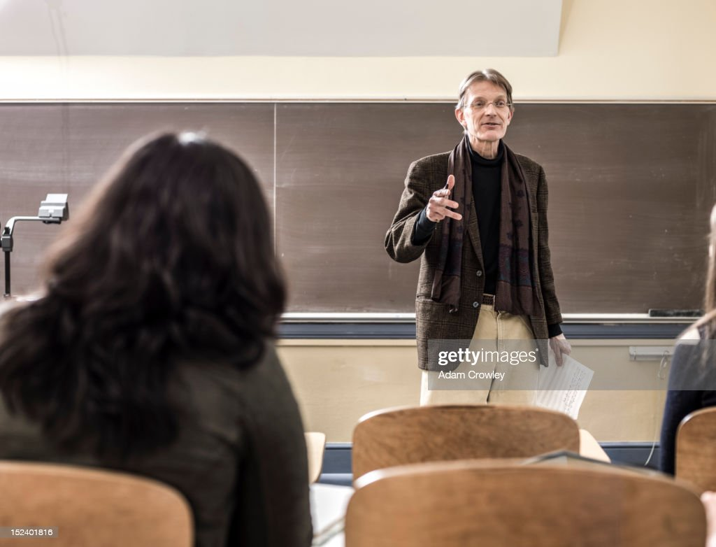 Teacher talking to students in classroom : Stock Photo