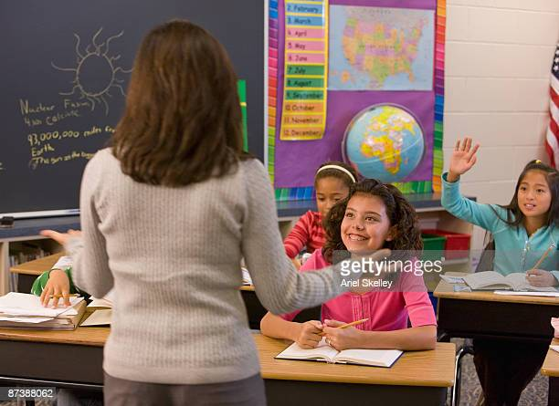 teacher talking to students in classroom - maestra foto e immagini stock