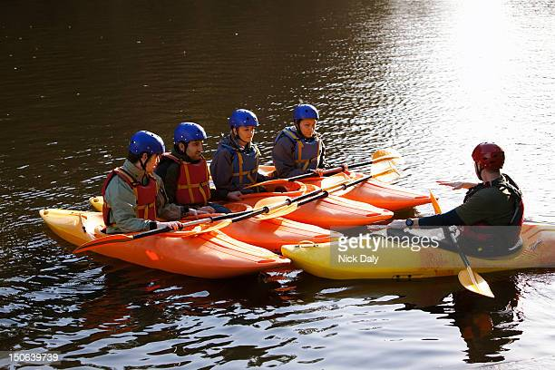 teacher talking to students in kayaks - water sport stock photos and pictures