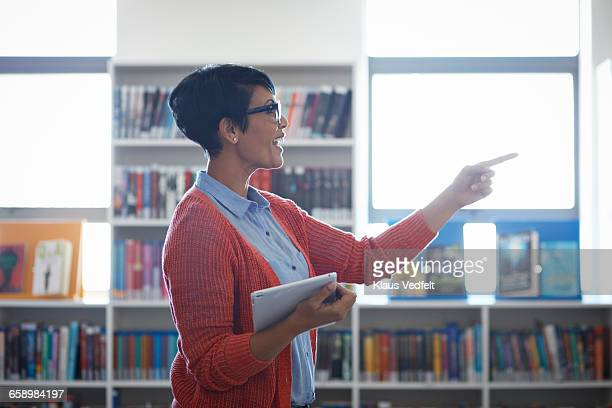Teacher talking to students, in the library