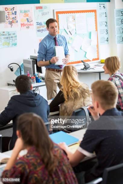 Teacher talking to teenage students in classroom