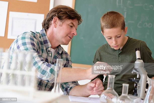 Teacher talking with student (8-9) in classroom