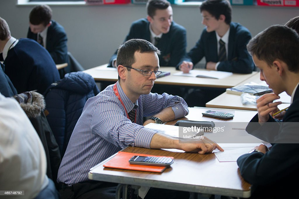 A teacher talks to a pupil during a maths lesson at the Ridings Federation Winterbourne International Academy in Winterbourne near Bristol on February 26, 2015 in South Gloucestershire, England. Education, along with National Health Service and the economy are likely to be key election issues in the forthcoming general election in May.