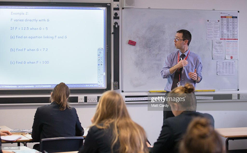 A teacher talks to pupils during a maths lesson at the Ridings Federation Winterbourne International Academy in Winterbourne near Bristol on February 26, 2015 in South Gloucestershire, England. Education, along with National Health Service and the economy are likely to be key election issues in the forthcoming general election in May.