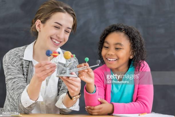 Enseignant parle avec jeune étudiante du système solaire
