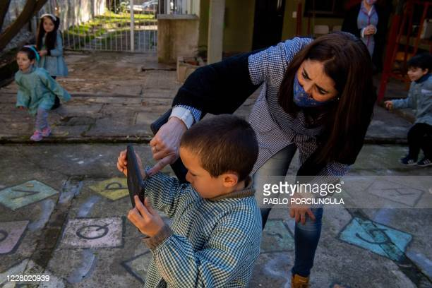 "Teacher teaches a pre-school boy to take pictures with his ""Ceibalita tablet"" during a class in a public school in Montevideo, amid the COVID-19..."