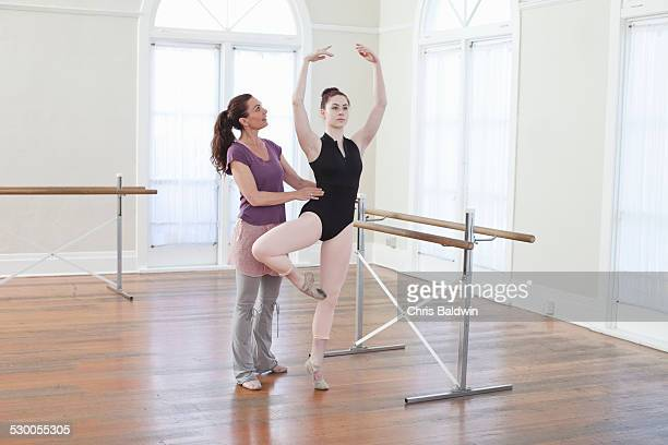 teacher teaching ballet position to teenage ballerina at ballet school - barre class stock photos and pictures