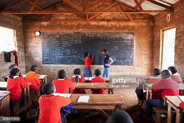 teacher teaching classroom of school children, kenya - native african girls stock pictures, royalty-free photos & images