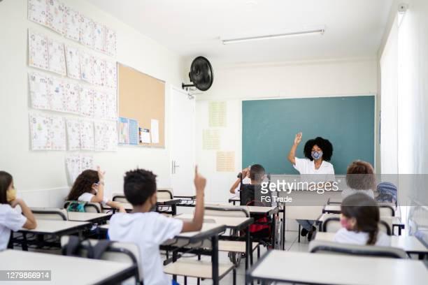 professor leciona em sala de aula respeitando o distanciamento social entre alunos - education - fotografias e filmes do acervo