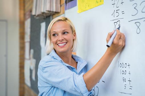 Teacher teaching math on whiteboard 950609434