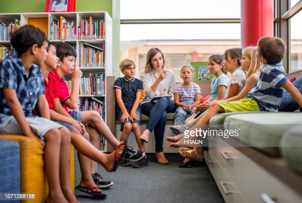 teacher teaching multi-ethnic students in library - elementary school stock pictures, royalty-free photos & images