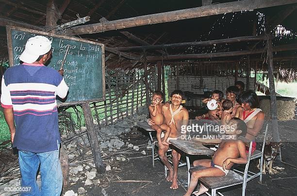 A teacher teaching reading to a group of Yanomami Indians from the Cavaroa tribe near the Siapa River Amazonas Guyana Venezuela