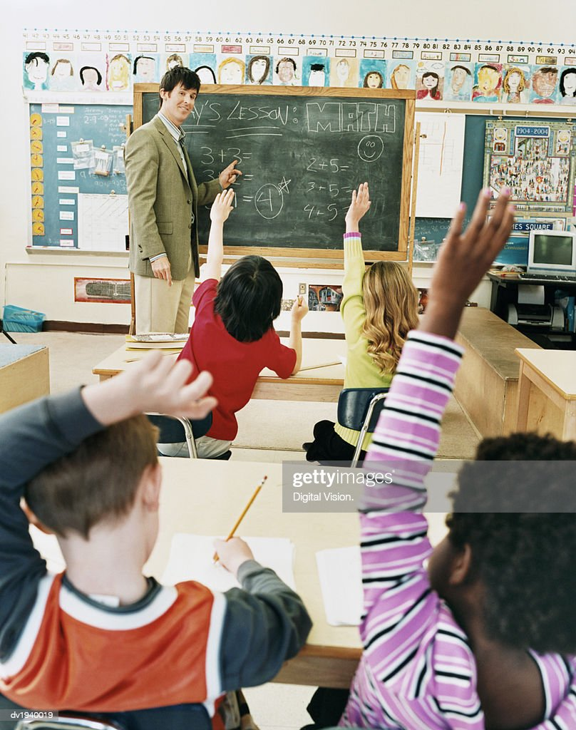 Teacher Teaching to Schoolboys and Girls With Their Hands Raised in a Classroom : Stock Photo