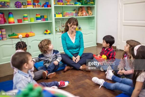 professora contando uma história para crianças no jardim de infância - narração de histórias - fotografias e filmes do acervo