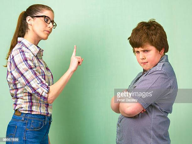 Teacher telling off overweight school boy