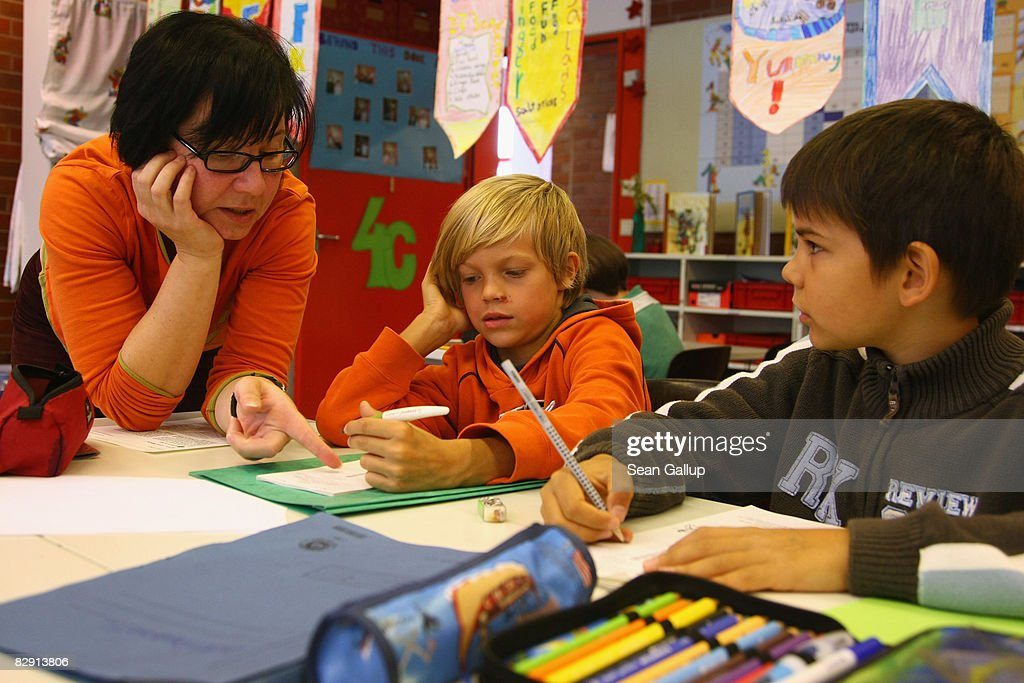 A teacher tends to fourth-grade children in a classroom in the elementary school at the John F. Kennedy Schule dual-language public school on September 18, 2008 in Berlin, Germany. The German government will host a summit on education in Germany scheduled for mid-October in Dresden. Germany has consistantly fallen behind in recent years in comparison to other European countries in the Pisa education surveys, and Education Minister Annette Schavan is pushing for an 8 percent increase in the national educaiton budget for 2009.