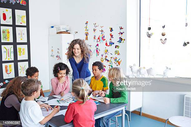 Teacher together with kids doing drawings