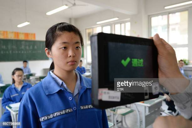 A teacher uses a machine which employs both fingerprint and facial recognition technology to check the identification of a student before a simulated...