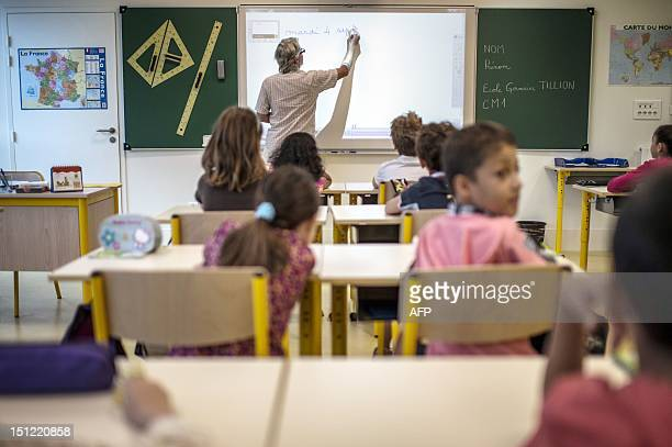 A teacher uses an interactive whiteboard in a classroom at Germaine Tillion primary school on September 4 2012 at the start of the new school year in...