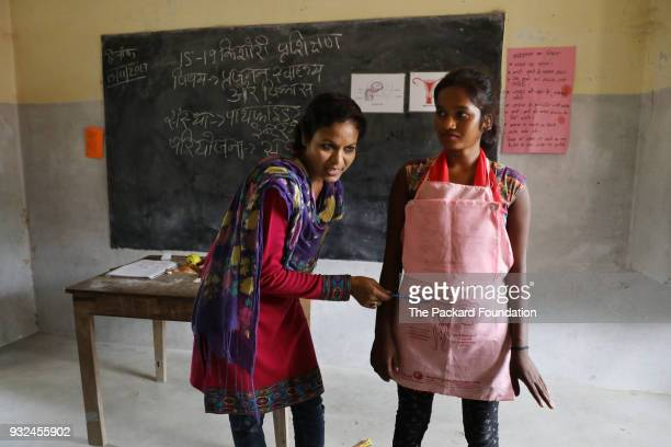 A teacher uses interactive tools to explain reproductive health systems to a classroom of unmarried adolescent girls The girls are learning about the...