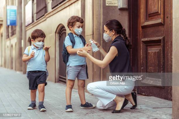teacher using hand sanitizer with kids going back to school - science and technology stock pictures, royalty-free photos & images