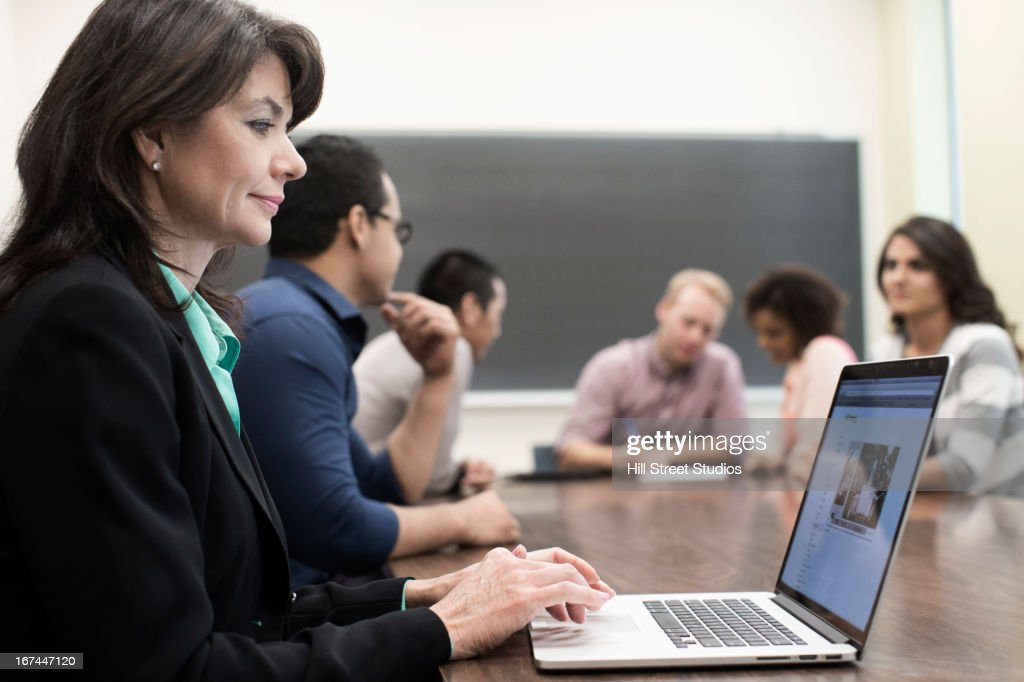 Teacher using laptop in classroom : Stock Photo