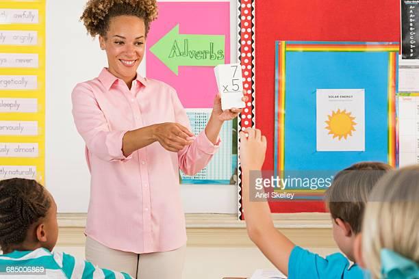 Teacher using multiplication flash cards in classroom