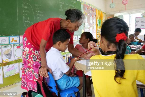 Teacher Valo Talava checks the work of Winisa Pop at Nauti Primary School on August 15 2018 in Funafuti Tuvalu The children learn in bith their...