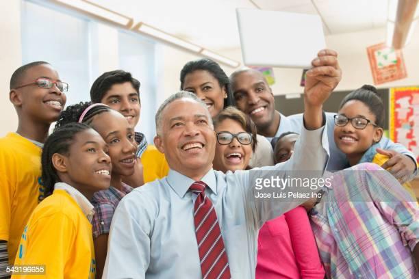 Teacher, volunteers and students taking selfie with digital tablet in classroom